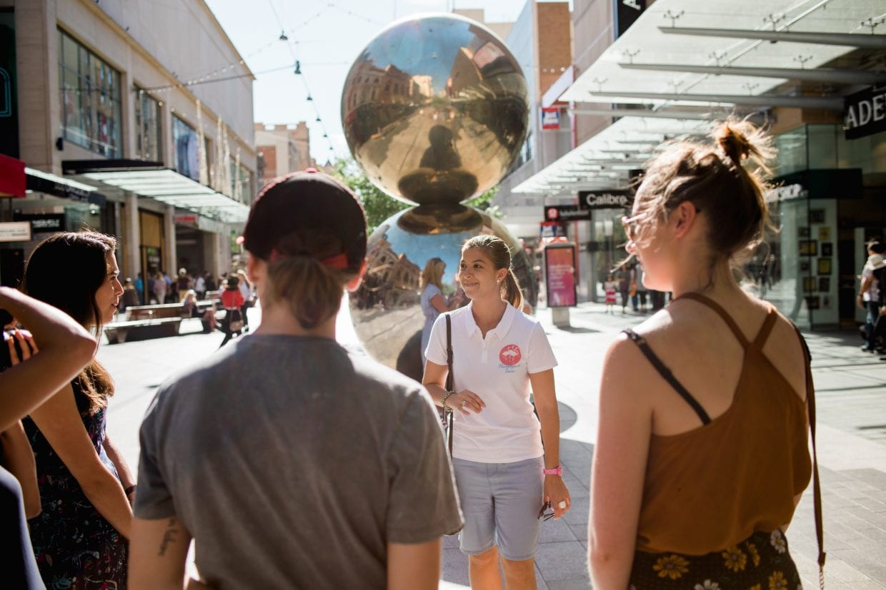 A guide explains the Mall's Balls sculpture in Rundle Mall to visitors in Adelaide.