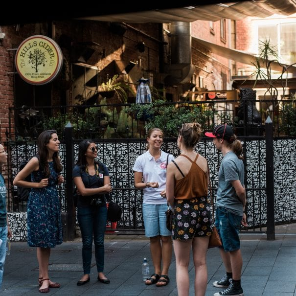A tour guide explains her surroundings to a small group of visitors to Adelaide.