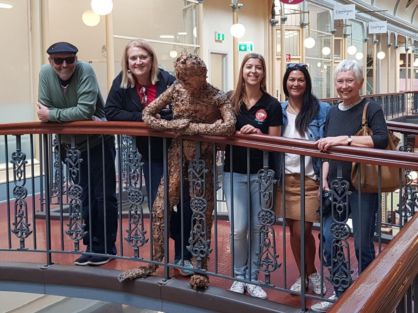 A group of four visitors with their tour guide pose in Adelaide Arcade.