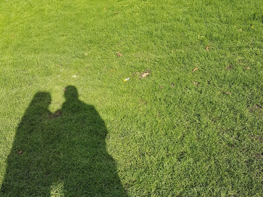 Shadows of two people on grass in Adelaide representing homelessness.