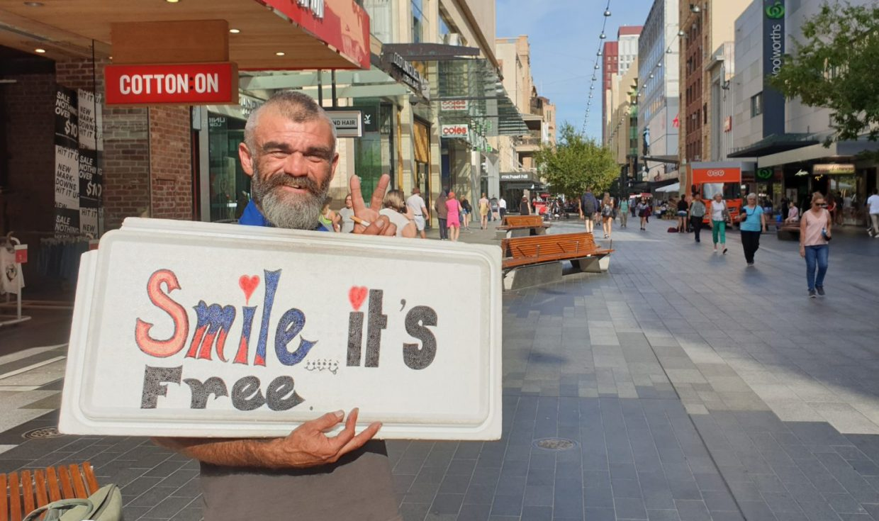 Stephen Coard holding his 'Smile, it's free' sign in Adelaide's Rundle Mall advocating mental health awareness.