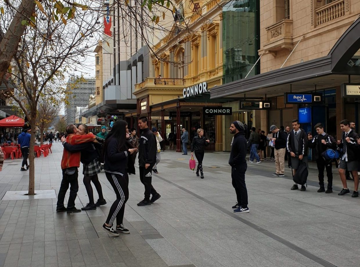 A man is hugged after holding a sign in Rundle Mall, Adelaide, which says Free Hugs.