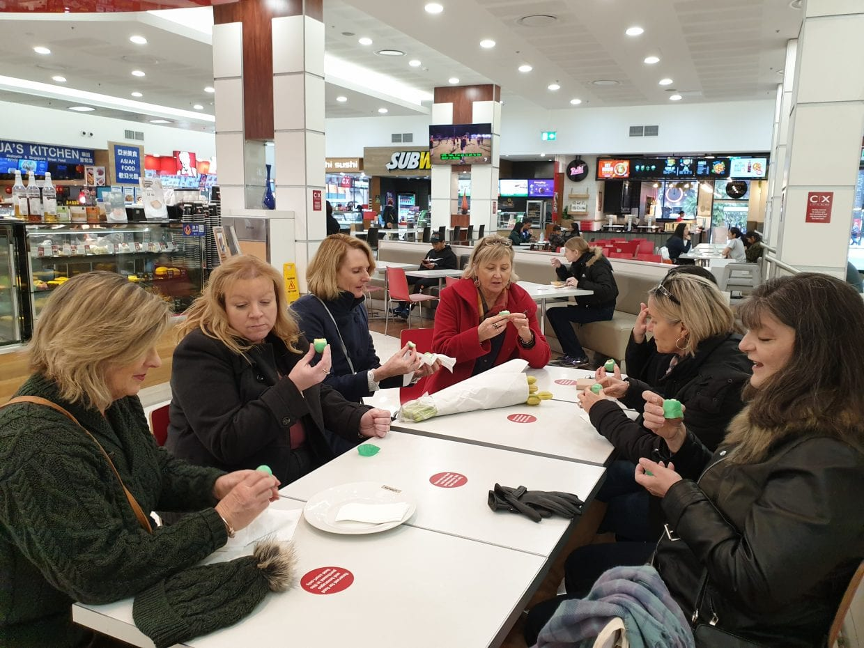 Adelaide residents trying a frog cake while on food tour The F Factor with Flamboyance Tours
