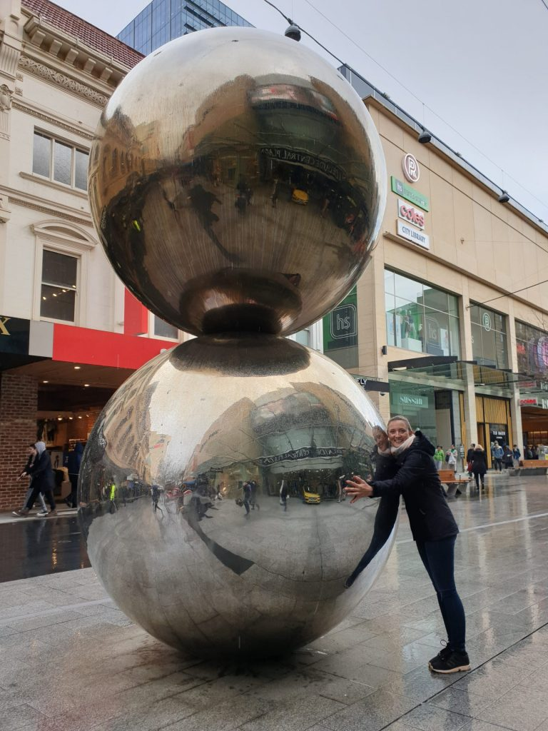 A young woman hugs the Mall's Balls sculpture in Adelaide's Rundle Mall