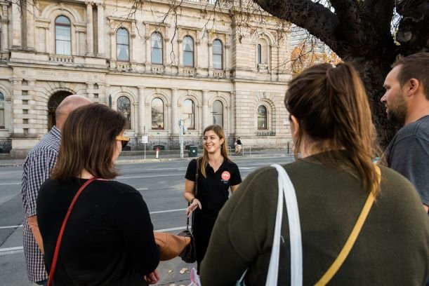 A tour guide from Flamboyance Tours showing tourists an Adelaide landmark.