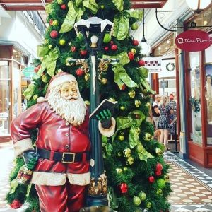 A Santa Claus statue posing by a Christmas tree in Adelaide Arcade.