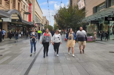 Five travellers walk along Rundle Mall on the Welcome To Adelaide walking tour.